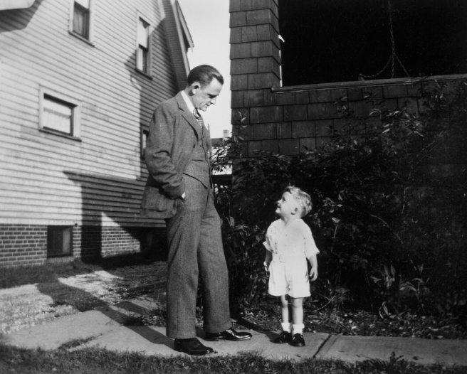 Father and son look at each other on sidewalk, ca. 1930.